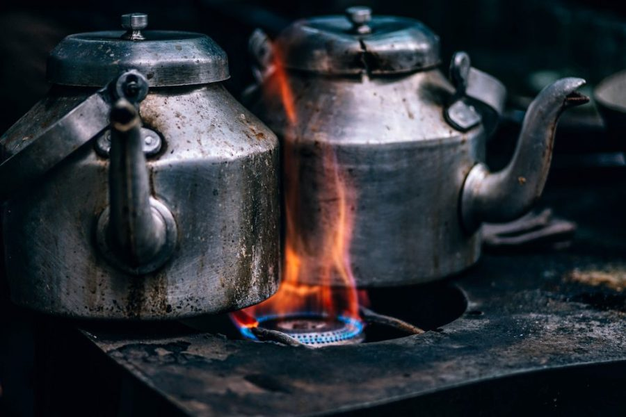 Tea kettles on a stove with a strong fire