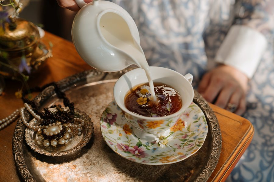 Person pouring milk over a cup of tea