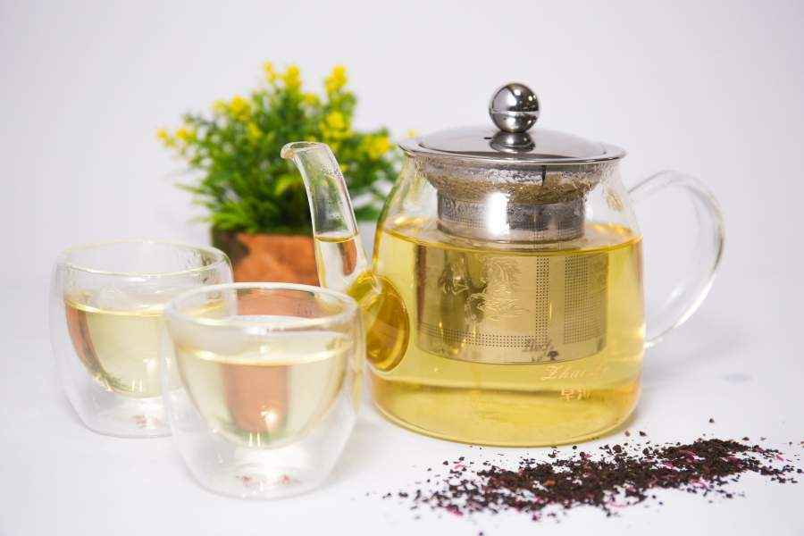 Two glass cups and a clear glass teapot with infuser