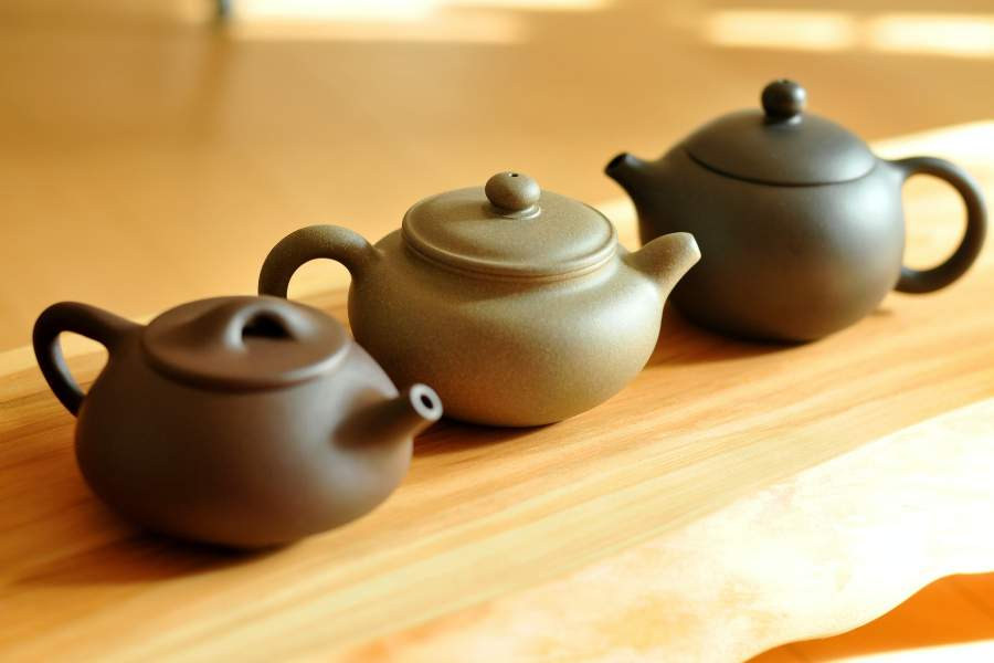 Three small clay teapots on a wooden table