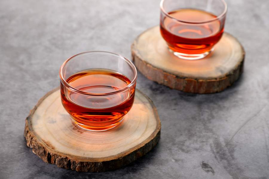 Two cups of black tea on wooden coasters