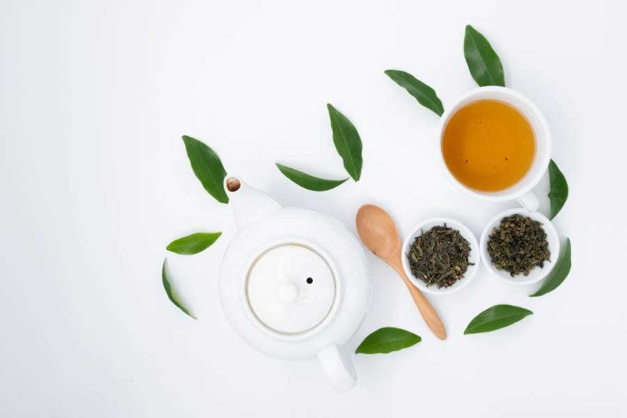 A tea pot, two small bowls of loose leaf, and a cup of green tea on a white surface