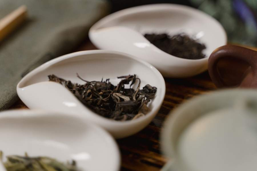 Black loose tea leaves on a white container