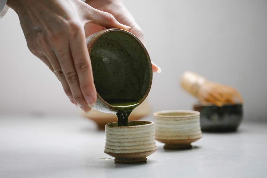 Person pouring matcha tea into a smaller cup