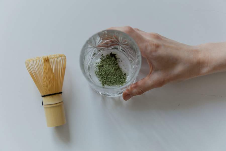 A whisk and a glass with matcha powder