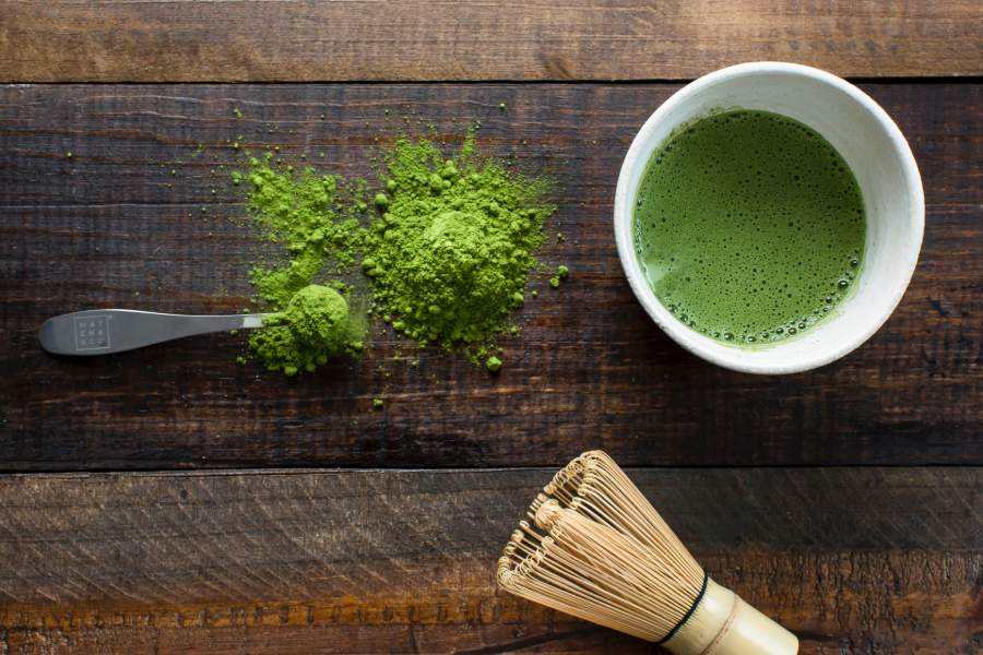 A cup of matcha green tea beside a whisk and a scoop of matcha powder