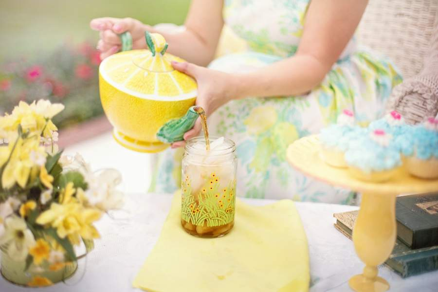 Woman pouring tea on a drinking glass with ice cubes