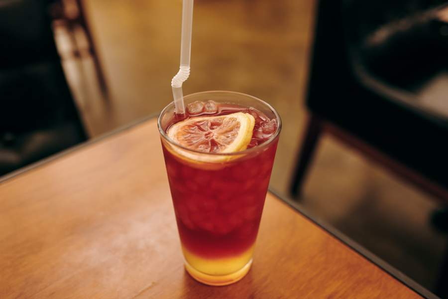 A glass of iced tea with a slice of lemon on top