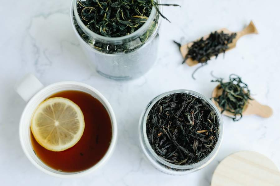 Two jars of loose tea leaves and a cup of tea with sliced lemon on top