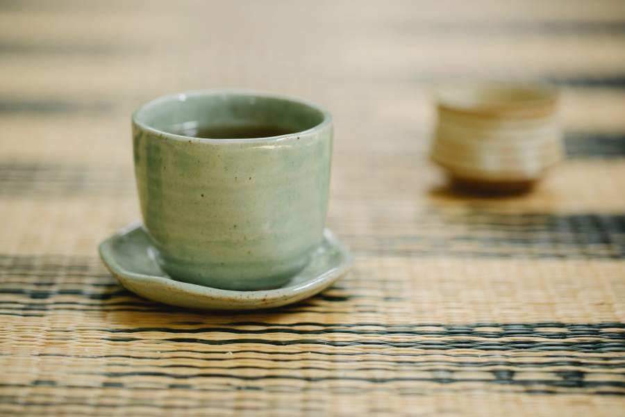 A green ceramic teacup filled with tea