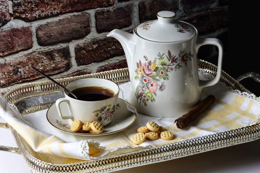 A cup of tea and a teapot placed on a rectangular tray